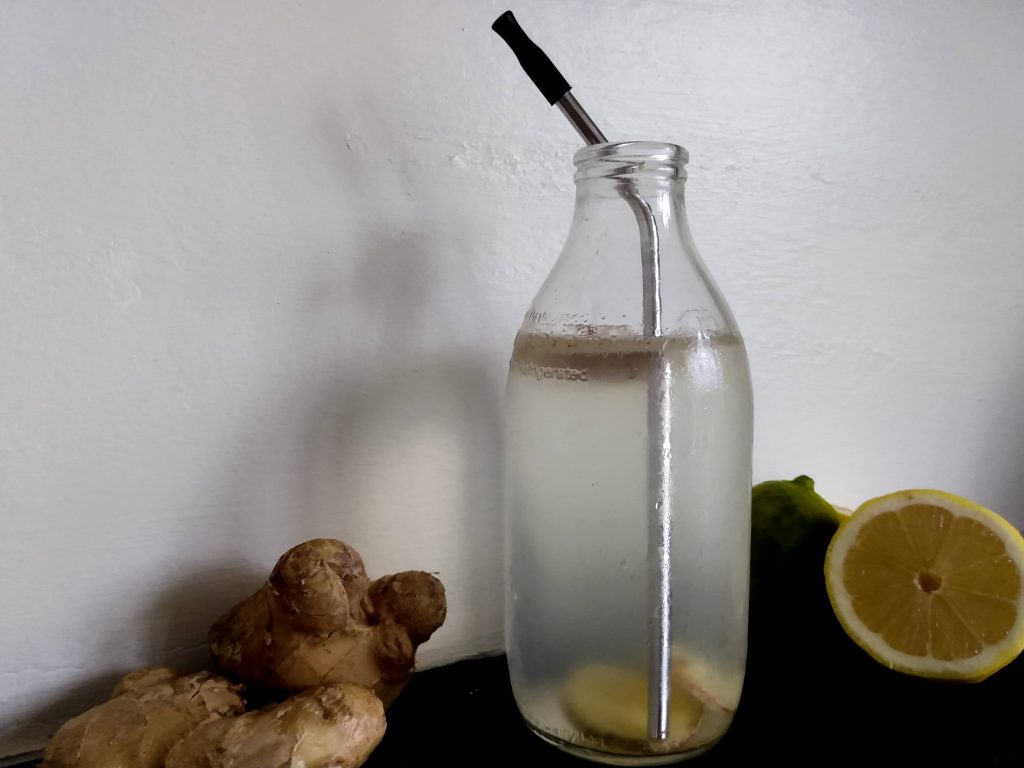Picture of glass bottle with lemon water in it. The Benefits of Drinking Lemon Water in the Morning by a Hopeful Home.