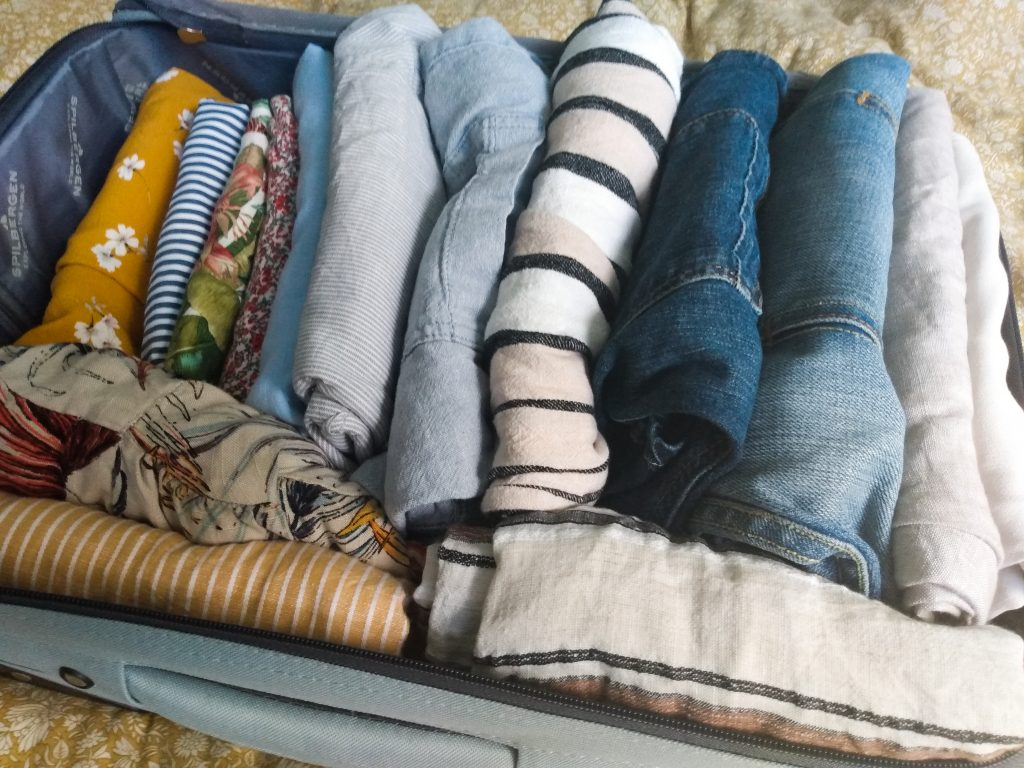 Header image of suitcase with summer wardrobe. As the Seasons Change By A Hopeful Home.